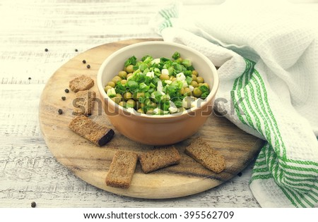 Canned peas with chives in ceramic bowl on wooden background. Healthy breakfast. Healthy food concept. Toned image. Soft view. - stock photo