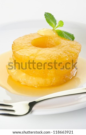 Canned pineapple rings fried in caramel sauce on a white plate