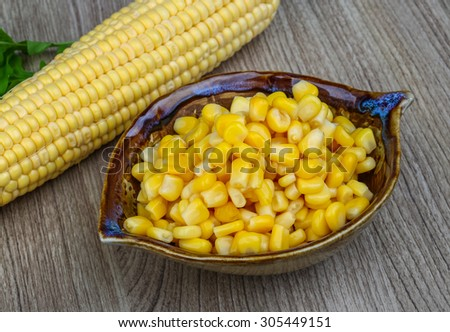 Canned sweet corn in the bowl on wood background
