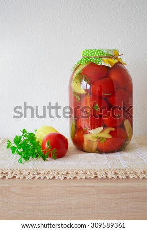 Canned tomatoes, homemade preserved vegetables on wooden table