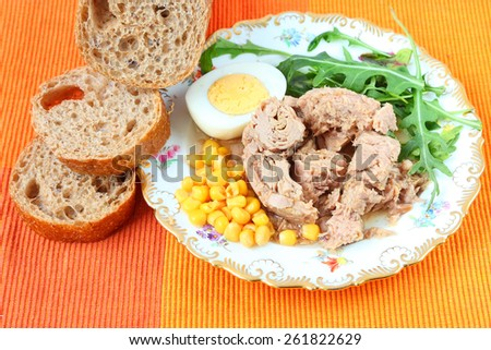 Canned tuna, sweet corn, boiled egg, sliced rye bread with bran and fresh salad leaves (rucola) on a bright color napkin. - stock photo
