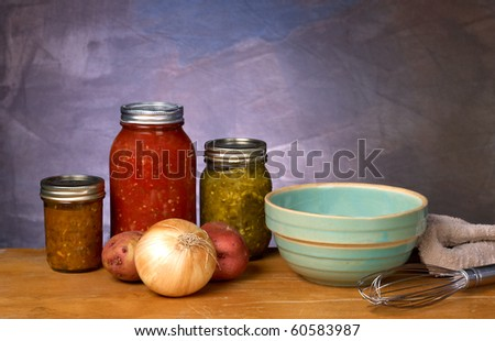 Canned vegetables and fruits in a kitchen set with bowl towel and whisk - stock photo