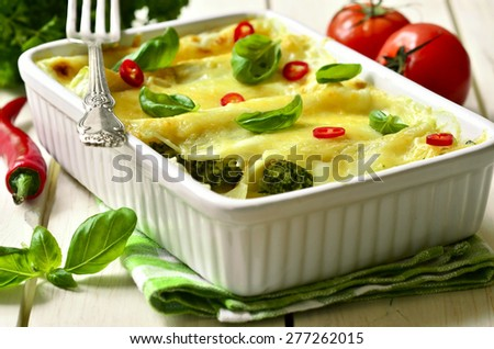 Cannelloni - baked pasta stuffed with spinach,chicken and cheese on a wooden table. - stock photo