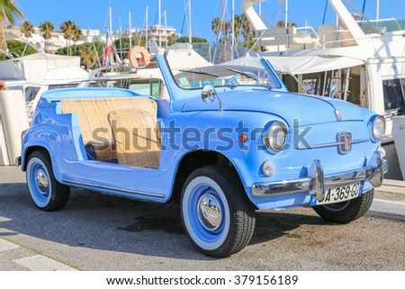 CANNES, FRANCE - 12 APRIL. 2015: A light blue Fiat 600 Jolly convertible with wicker seats is parked in the harbour of Cannes, France. - stock photo