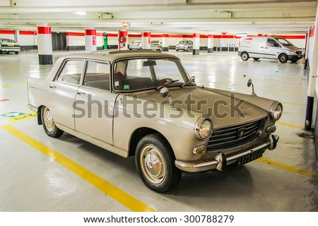 CANNES, FRANCE - AUGUST 3, 2014: Beige retro car Peugeot 404 at the underground parking. - stock photo