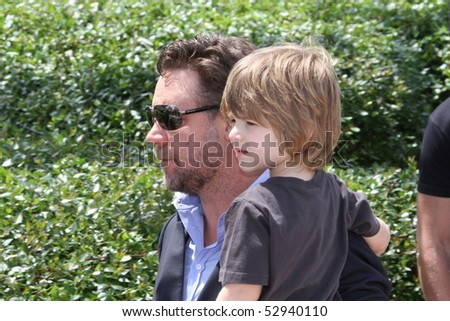 CANNES, FRANCE - MAY 12: Actor Russell Crowe carries his son Tennyson Crowe at the 'Robin Hood' Photocall held at the Palais  during the 63 Cannes  Festival on May 12, 2010 in Cannes, France. - stock photo