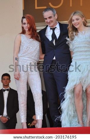 """CANNES, FRANCE - MAY 23, 2014: Kristen Stewart, Chloe Grace Moretz & director Olivier Assayas at gala premiere of their movie """"Clouds of Sils Maria"""" at the 67th Festival de Cannes.  - stock photo"""