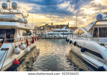 CANNES, FRANCE - MAY 02, 2012: Large luxury yacht in the famous bay, during a beautiful sunset, May 02, 2012 in Cannes, France. - stock photo