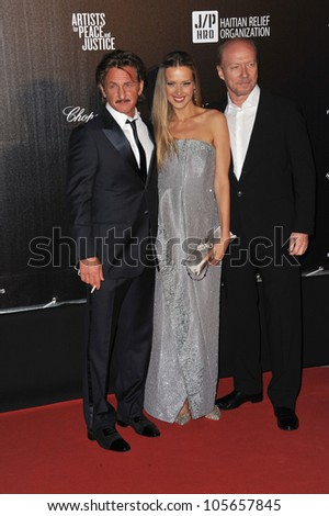 "CANNES, FRANCE - MAY 18, 2012: LtoR: Sean Penn, Petra Nemcova & Paul Haggis at the ""Haiti Carnaval in Cannes"" party at the 65th Festival de Cannes. May 18, 2012  Cannes, France"