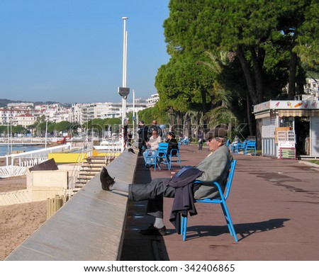 CANNES, FRANCE - NOVEMBER 3, 2003: People taking a rest at the Boulevard de la Croisette on November 3, 2003 in Cannes, Cote d'Azur, France