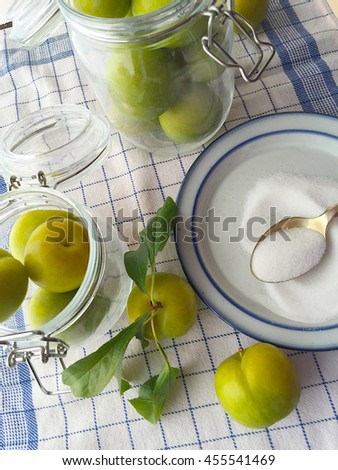 Canning jars, green plums and sugar on a blue and white dish towel - stock photo