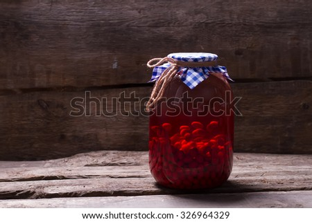 Canning juice in the dark  cellar. Homemade compote of dogwood on wooden boards. Natural drink on an old wooden shelf. Canning juice in the dark  cellar. - stock photo