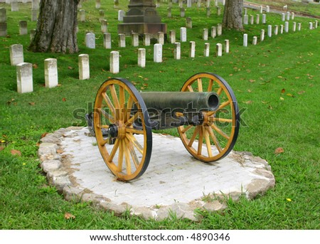 cannon in front of veteran's tombstones - stock photo
