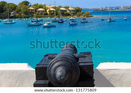Cannon pointing at ships in the Caribbean Sea - stock photo