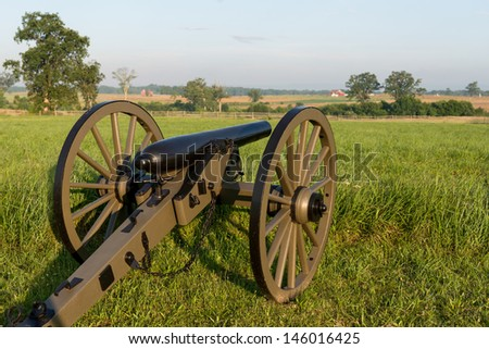 Cannon positioned toward a red barn at the Gettysburg National Military Park in Pennsylvania - stock photo