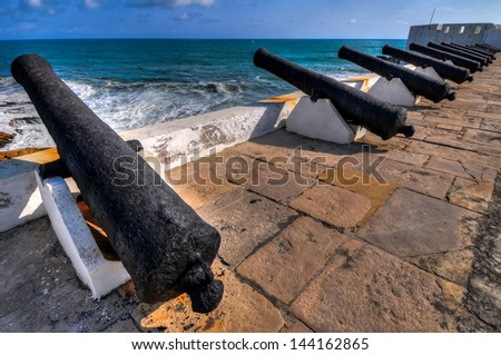 Cannons overlooking from Cape Coast Castle, a fortification in Ghana built by Swedish traders for trade in timber and gold. Later the structure was used in the trans-Atlantic slave trade. - stock photo