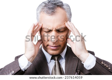 Cannot resist it. Frustrated mature man in formalwear touching head with fingers and keeping eyes closed while standing against white background - stock photo