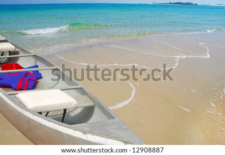 Canoe docked on beach with pretty water and calm waves - stock photo