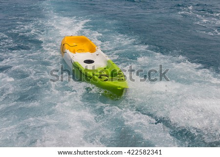 Canoe floating in the sea by strong waves. - stock photo