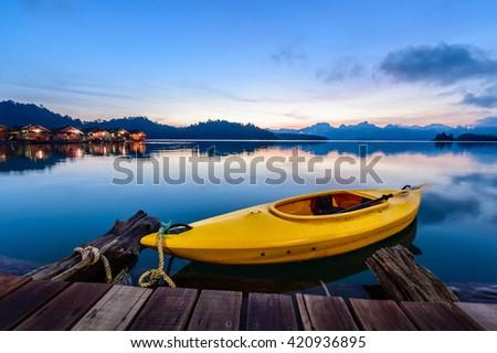 Canoe floating on the calm water under amazing sunrise - stock photo