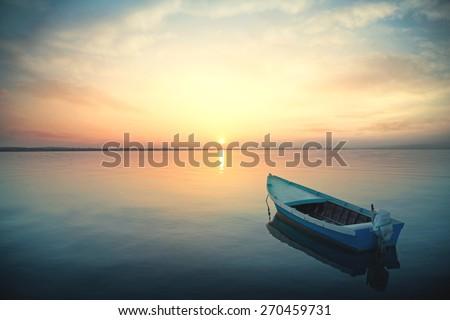 Canoe floating on the calm water under amazing sunset - stock photo