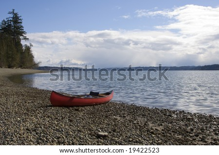Canoe grounded on the shores of Burfoot Park with the waters of Budd Inlet (South end of the Puget Sound) leading to the Capital City of Olympia Washington in the distance.