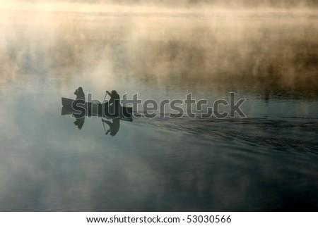 Canoe in the morning mist - stock photo