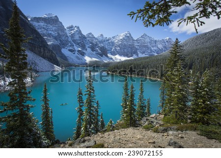 Canoe on beautiful Moraine Lake in Banff National Park with light dusting of snow. Valley of the Ten Peaks, Canadian Rocky Mountains, Alberta, Canada - stock photo