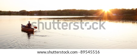 Canoe on Lake with Setting Sun