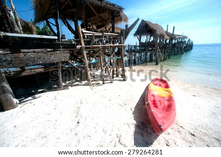 Canoe on the beach and traditional wooden bridge. - stock photo
