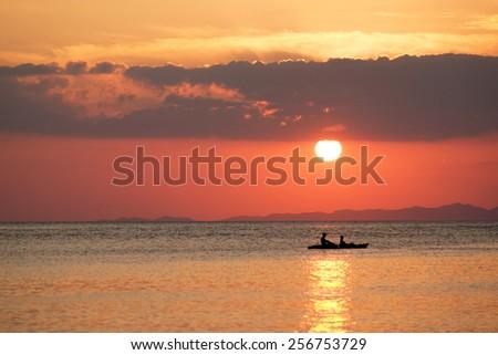 Canoe on the ocean at sunset - stock photo