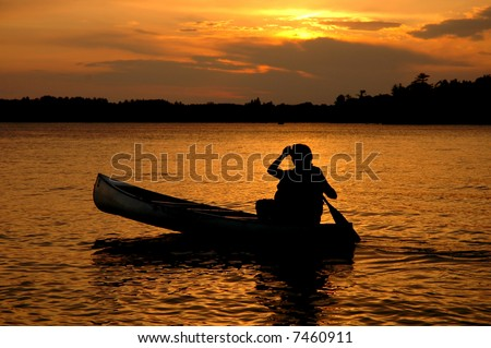 Canoe Silhouette in Sunset on a Minnesota Lake - stock photo