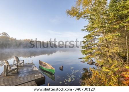 Canoe Tied to a Dock at Dawn - Haliburton, Ontario, Canada - stock photo