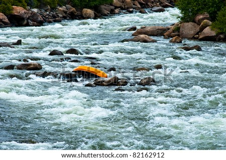 "canoe upside down in middle of river conceptualizing ""up the creek with out a paddle"" - stock photo"