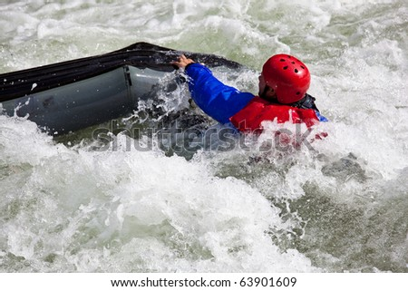 Canoeing in white water in rapids on river with the canoeist falling out of his boat - stock photo