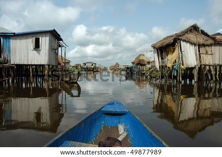 Canoeing through the stilt village of Ganvie in Benin - stock photo