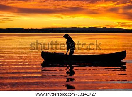 Canoeist at sunset - stock photo