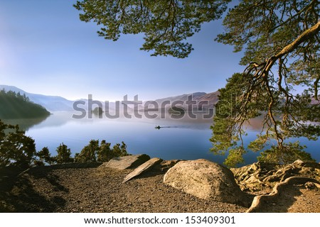 Canoeist Paddles on Derwent Water English Lake District on Sunny Winters Day /Derwent Water Canoeist. - stock photo