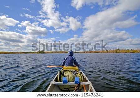 Canoer on Seagull Lake in the Boundary Waters in Fall - stock photo