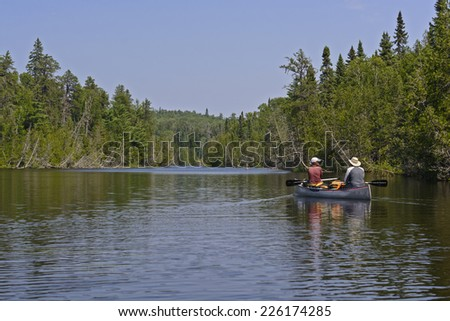 Canoers heading into Bit Lake in Quetico Provincial park - stock photo