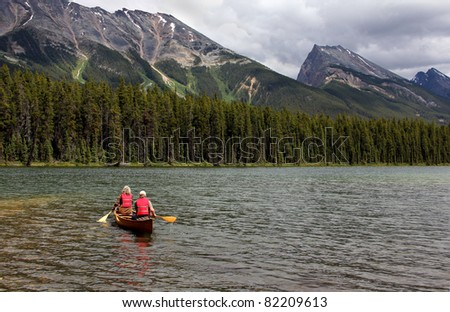 Canoers on Honeymoon Lake with view of the Endless Ridge Chain mountain range located in Jasper National Park, Alberta, Canada.