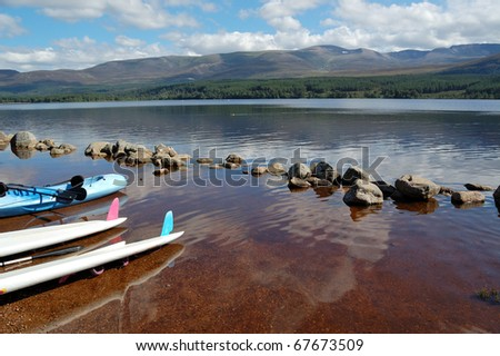 canoes at the edge of loch morlich in the highlands of scotland - stock photo