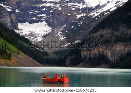 Canoes in serene lake - stock photo