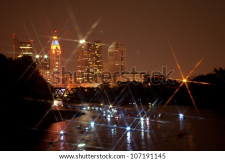 Canoes light up the Scioto river in Columbus Ohio after the fireworks show. A star filter was used for effect. - stock photo