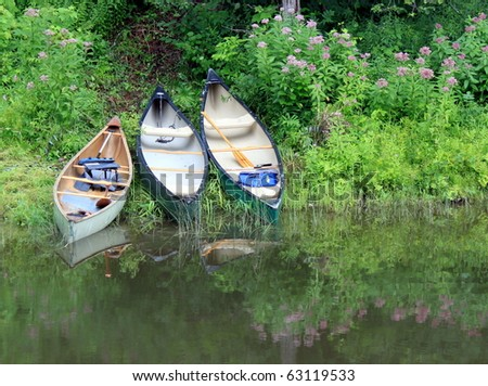 Canoes on the Riverbank - stock photo