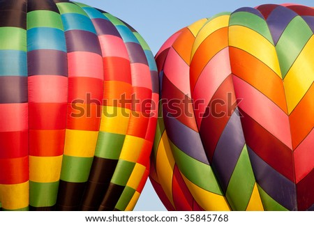 Canopies of two hot air balloons bounce against each other during inflation - stock photo