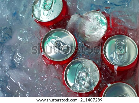cans of drink on crushed ice - stock photo
