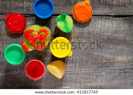 Cans of paint and brush on a dark wooden background, children's creative drawing. - stock photo