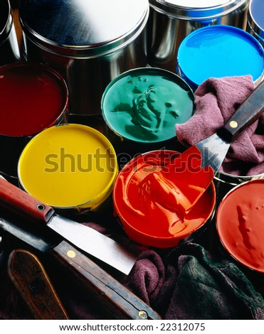 Cans of printing inks with ink knives and wipers - stock photo