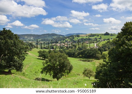 Cantabria landscape, typical valley with little town rounded by pastures and trees. Spain